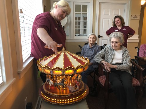 Circus Music plays out of the Carousal. The residents sing to the music and discuss memories of the Circus.
