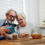 Older couple looking at smartphone at kitchen table.