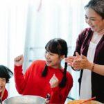 An older grandma in kitchen cooking with her grandchildren.