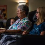 Grandma sitting with her two grandchildren on a couch watching a movie.
