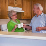 Older couple in kitchen having a cup of coffee.