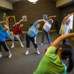 Residents stretching during senior living activities