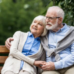 smiling senior couple embracing while sitting on wooden bench in
