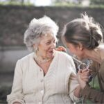 Older adult smiling with adult daughter; memory care.