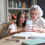 Older woman looking at smartphone with granddaughter.