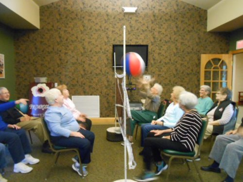 Residents are trying to figure out which way the ball is going while playing chair volleyball.