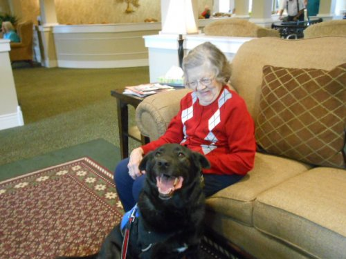 Lois visiting with Duffy, a therapy dog visiting the residents.