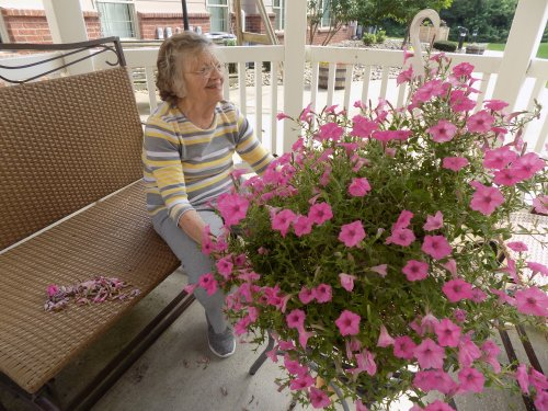Lois taking care of her outdoor hanging basket!