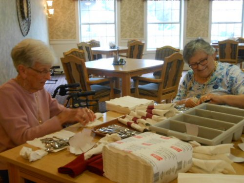 Dolores and Kelly are wrapping silverware so we can eat supper!