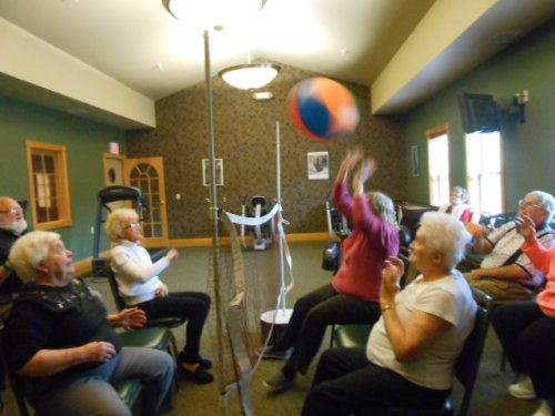 Jean is hitting the beach ball over the net while playing chair volleyball.